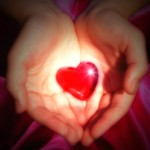 hands cupping a red Valentine heart